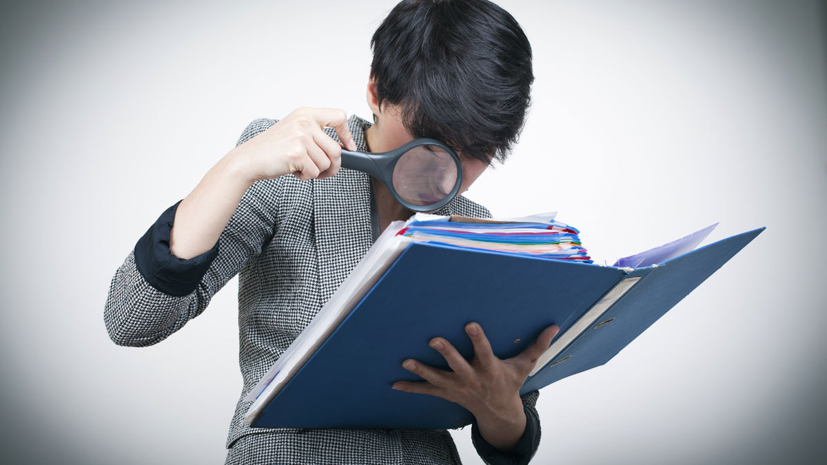 Woman with magnifying Glass Looking at Files