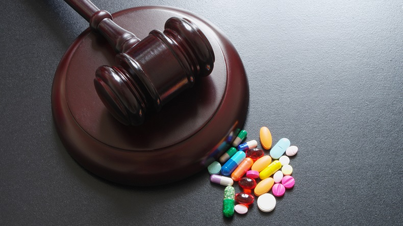 Wooden judge gavel with drugs on table